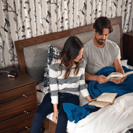 Couple reading books in bed.