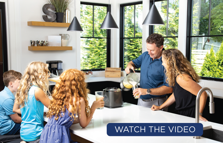 Family making smoothie in kitchen. Father pours smoothie into glass while daughter is sitting drinking smoothie. Button reading WATCH THE VIDEO.